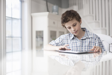 A boy seated at a table using a digital tablet, hand on the touch screen.