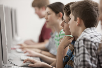A group of young people, boys and girls, students in a computer class working at screens.