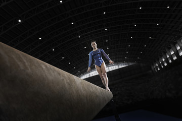 A gymnast with her arms by her side on a balance beam
