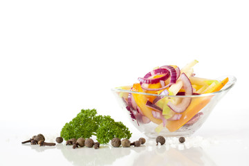 Salad with fresh onion and vegetables in glass plate, green parsley, peper, rosemary on white background