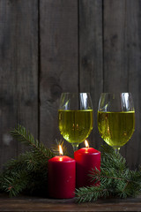 Christmas candles and lights. Two burning candles in with baubles and fir branch over wooden background, still life