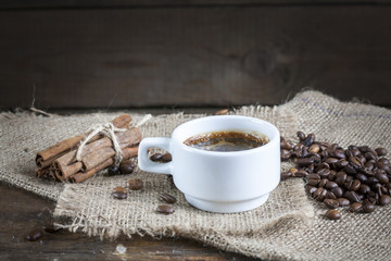 Coffee cup, cinnamon and coffee beans on a wooden background.