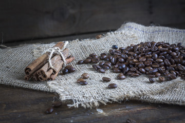 Coffee beans and cinnamon on a wooden background