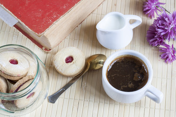 Cup of hot coffee with books, milk and flowers on wooden table. Vintage still life.