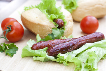 Hot dog. Grilled hot dogs with fresh salad lettuce on wooden table.