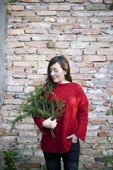 A woman holding in her arms pine branches for to make a christmas garland in front of a brick wall