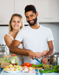 Interracial couple cooking vegetables