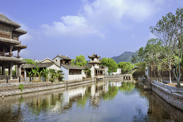 Traditional white Chinese houses reflected in a tranquil canal, Hengdian, China