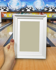 Wooden frame in woman hands on the background of bowling lanes