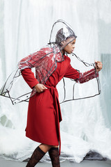 Beautiful young girl in red coat and rain coat posing in the studio