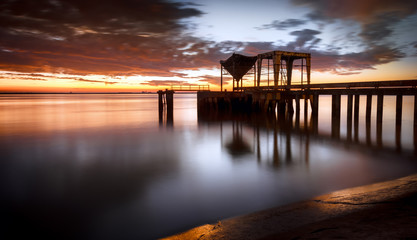 Ancient industrial pier over a sunrise