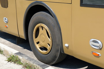Wheel of the yellow bus near the curb