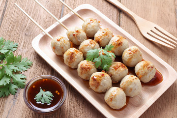 Grill pork balls pour with sweet spicy sauce on wooden table