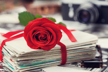 Stack of postcard and photograph tied with velvet ribbon and red rose, film and vintage camera