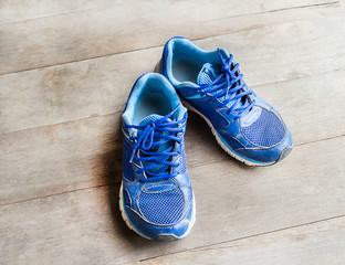 blue running shoes laid on a wooden floor
