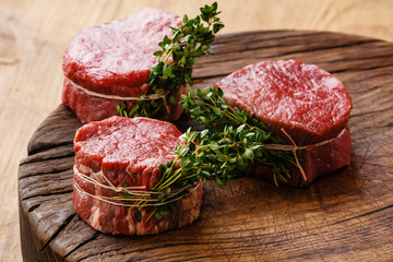 Raw fresh marbled meat Steak filet mignon and thyme on wooden ba