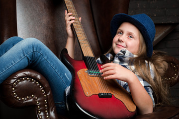 Little girl in hat playing guitar