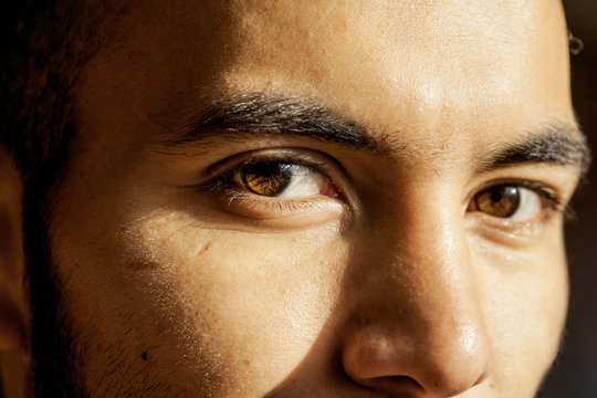 Man's brown eyes looking into the camera