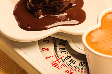 Coffee and chocolate cake on weighing scale.