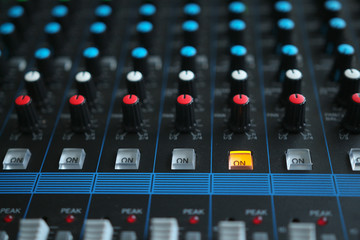 Close up of the rows of knobs and sliders on an analogue mixing