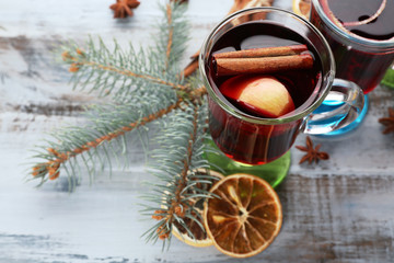 Tasty mulled wine and spices, on blue wooden background, close-up