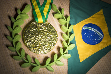 Gold medal surrounded by laurel wreath resting on tropical wood background with pennant Brazil flag with studio lighting