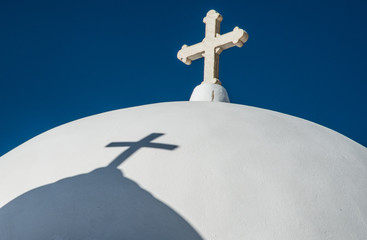A cross and a shadow of another cross atop a Greek Orthodox church near Fira town on the island of Santorini