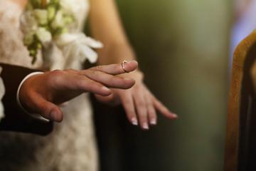Silver elegant wedding ring on groom finger in church closeup