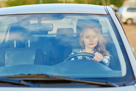 Young confident woman driving a car