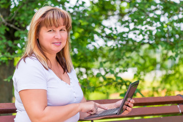 joyful mature woman on a park bench with a laptop