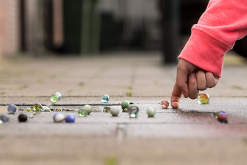 Child playing with marbles on yhe sidewalk.