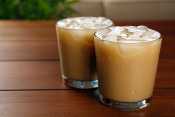 Cups of ice coffee on wooden table