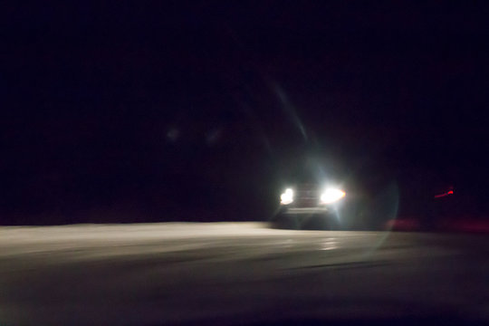 Headlights on a car, winter driving in the dark