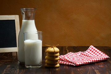 Still life of glass milk on wooden table with cookies