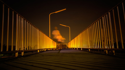 Footbridge with light reflection and motion blur of man walking