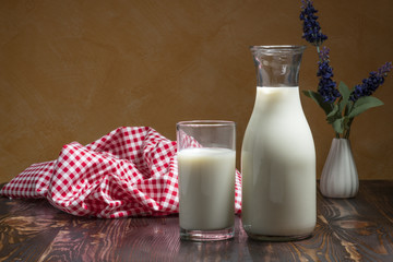 Milk bottle and milk glass put on wooden table.