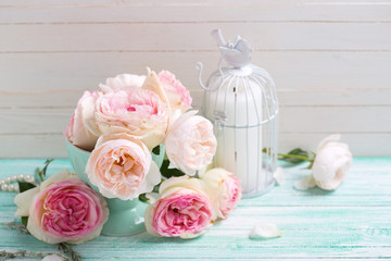 Background with sweet pink roses in vase and candle