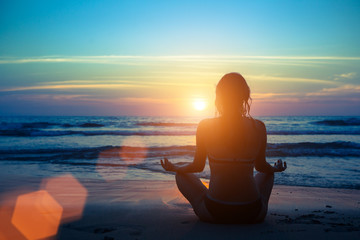 Obraz Silhouette young woman practicing yoga on the beach at sunset. - fototapety do salonu