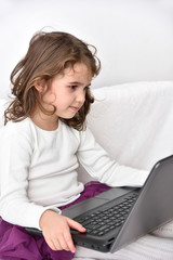 Cute young girl watching the cartoon on a laptop at home