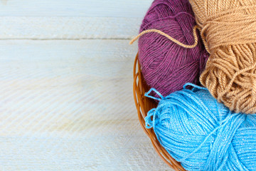 yarns for knitting in a wicker basket on white wooden table