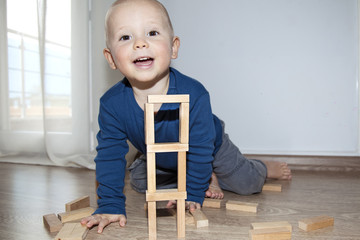 Little boy playing on the floor with wooden cubes.
