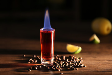 Burning cocktails with lime and coffee beans on a table