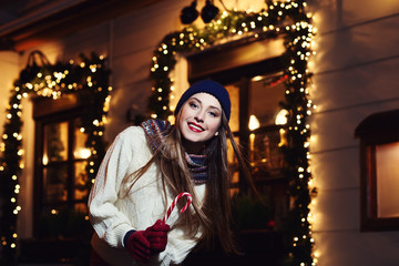 Night street portrait of smiling  beautiful young woman with Christmas candy cane. Model looking at camera. Lady wearing classic winter knitted clothes. Festive garland lights.