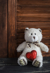 Toy bear and red heart on a dark wooden surface. Valentine's day gift. Holiday background