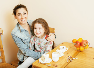 young mother with daughter on kitchen drinking tea together hugging eating celebration cake