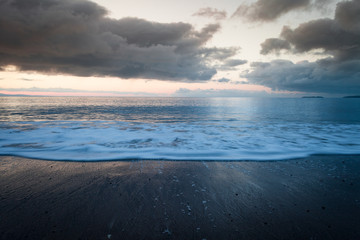 Rainy Sunrise Clouds over Coastal Beach with Wave in Motion