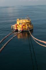 Oil tanker is transferring oil to the cargo vessel