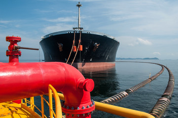 Oil tanker is transferring oil to the cargo vessel