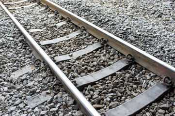 Metal railway tracks and sleepers with stone background