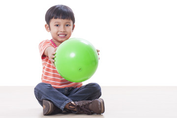 Little boy playing green ball